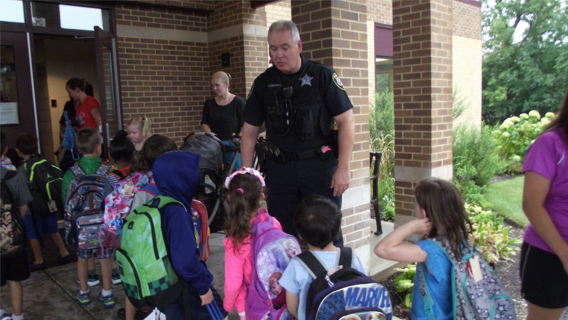Police Officer Greets Children During Morning Arrival